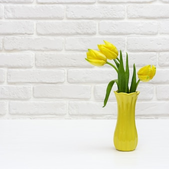 Żółte tulipany w wazonie. jasne wiosenne kwitnące kwiaty na białym murem ozdobnym.
