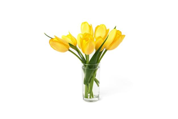 Żółte tulipany w wazonie na białym tle.