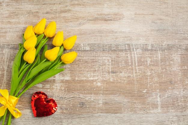 Żółte tulipany z czerwonym sercem na walentynki
