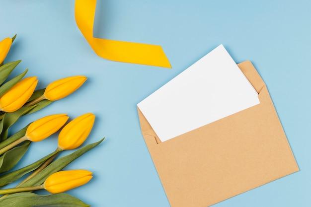 Żółte tulipany z pustą kartą w kopercie
