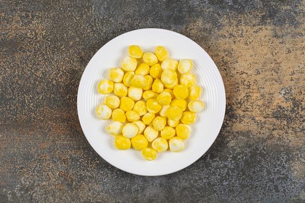 Żółte twarde cukierki na białym talerzu.
