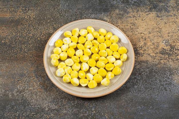 Żółte twarde cukierki na talerzu ceramicznym.