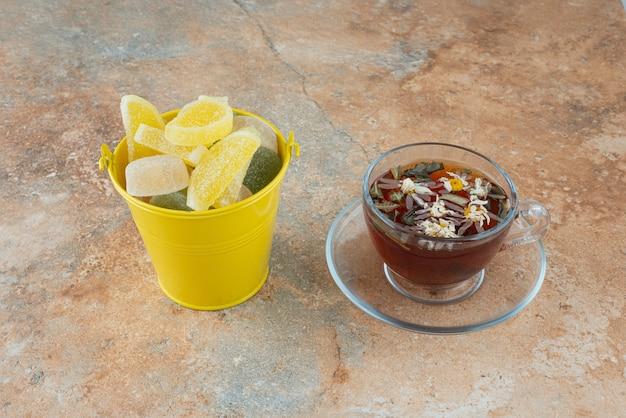 Żółte wiadro pełne cukierków z galaretką i filiżanką herbaty ziołowej