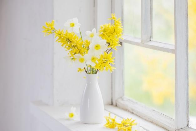 Żółte wiosenne kwiaty na starym białym oknie