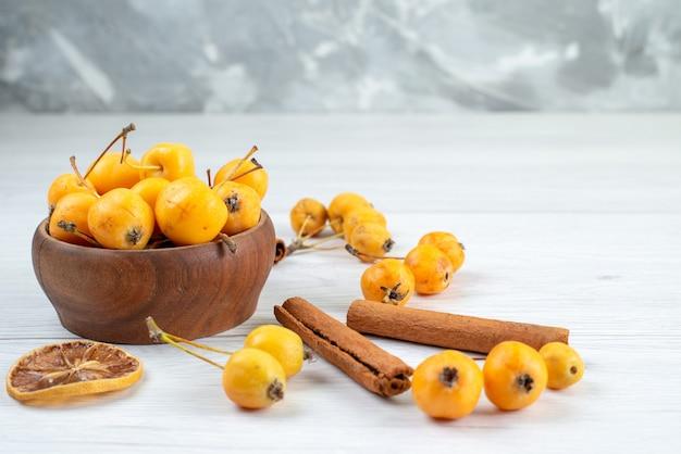 Żółte wiśnie łagodne i świeże wraz z cynamonem na świetle