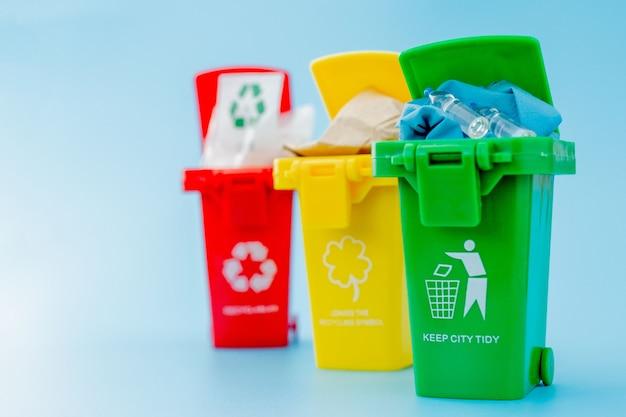 Żółte, zielone i czerwone kosze do recyklingu z symbolem recyklingu na niebieskim tle. utrzymuj porządek w mieście, pozostawia symbol recyklingu. koncepcja ochrony przyrody.