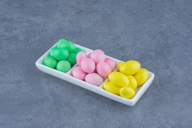 Żółte, zielone i różowe dziąsła na talerzu, na marmurowym tle.
