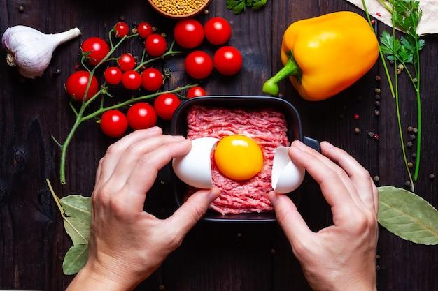 Żółtko na mielonej wieprzowinie w czarnym talerzu na drewnianym stole z pomidorkami koktajlowymi z przyprawami czosnk...