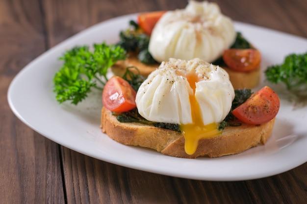 Żółtko spływające z jajka w koszulce na kromce chleba w białym talerzu na drewnianym stole. wegetariańska przekąska z jajkiem w koszulce.