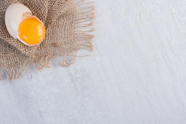 Żółtko w pękniętej skorupce na kawałku materiału na marmurowym stole.