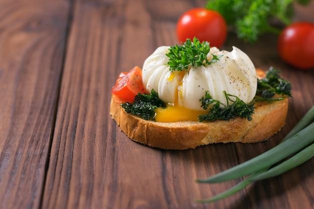 Żółtko wypływające z jajka w koszulce na kawałek chleba na drewnianym stole. wegetariańska przekąska z jajkiem w koszulce.