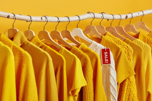 Żółto-białe ubrania w sprzedaży wieszaki na stojakach na żywym tle. duża wyprzedaż i zakupy.