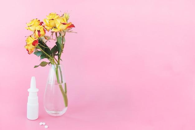 Żółto-czerwono-pomarańczowe róże w sprayu w szklanym wazonie z wodą, spray do nosa, trzy tabletki na różowym tle