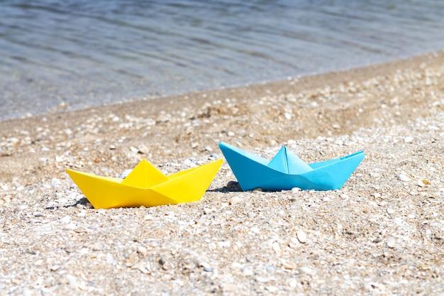 Żółto-niebieskie papierowe łódki origami na plaży