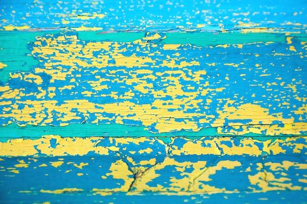Żółto-niebiesko-zielona łuszcząca się farba. drewniana powierzchnia pokryta kilkoma warstwami popękanej farby