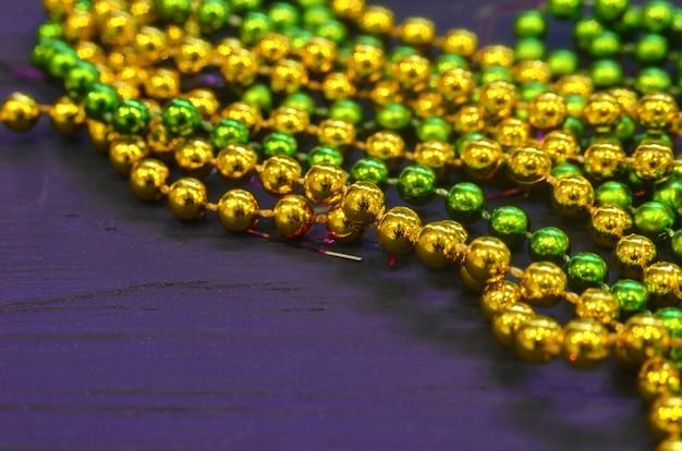 Żółto-zielone koraliki na fioletowym stole.