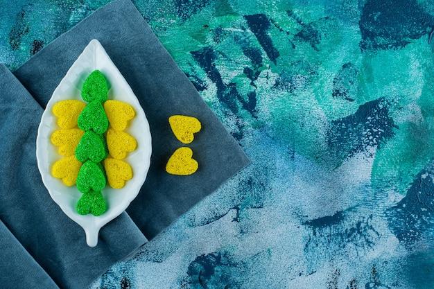Żółto-zielone słodkie ciasteczka na talerzu na kawałkach materiału, na niebieskim tle.