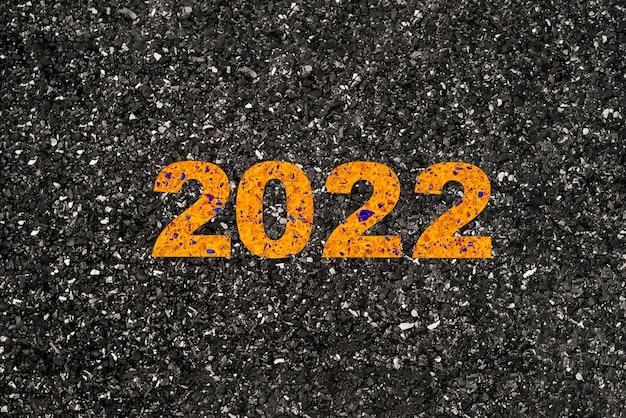Żółty 2022 rok na asfaltowej drodze do rozpoczęcia koncepcji wesołych świąt i szczęśliwego nowego roku.