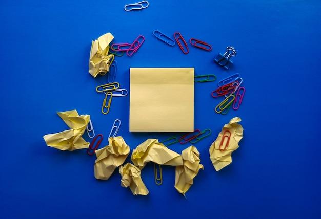 Żółty arkusz papieru na notatki i spinacz do papieru.