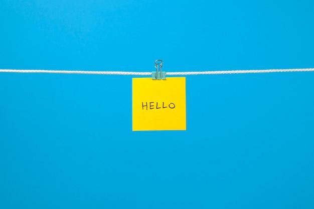 Żółty arkusz papieru na sznurku z tekstem hello