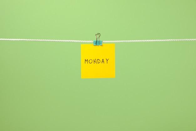 Żółty arkusz papieru na sznurku z tekstem poniedziałek