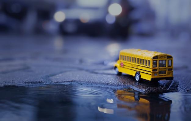 Żółty autobus szkolny (model zabawki) podczas ulewnego deszczu w mieście, niski kąt widzenia i niewielka głębia ostrości kompozycji.