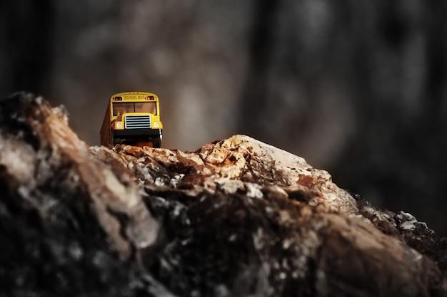 Żółty autobus szkolny (model zabawki) przechodzący przez wiejską drogę.