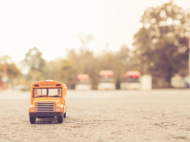 Żółty autobus szkolny plastikowy i metalowy model zabawki na wiejskiej drodze