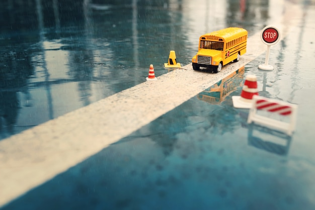 Żółty autobus szkolny zabawka model na drodze z znakami drogowymi, deszczowy dzień.