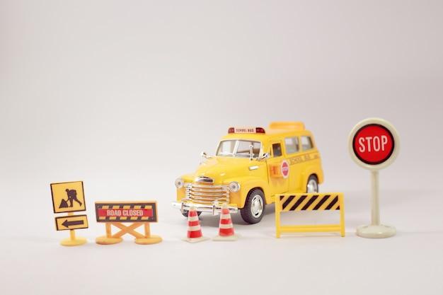 Żółty autobus szkolny ze znakami drogowymi na skrzyżowaniu dróg.