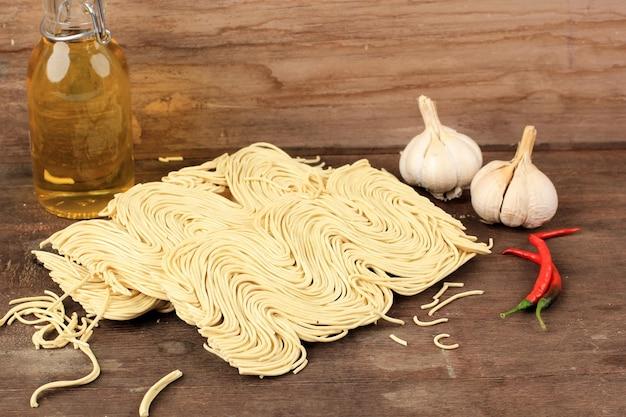 Żółty azjatycki suchy makaron, indonezyjski typowo makaron zwany bakmi. gotowy do przyrządzenia z domową przyprawą. w indonezji popularne jako mie telor lub bakmi