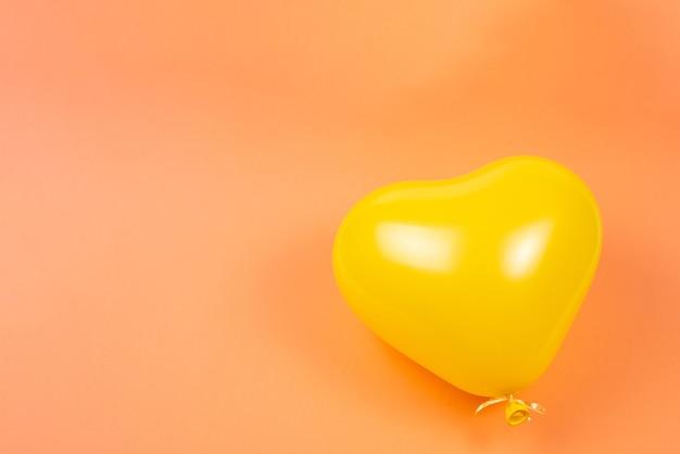 Żółty balon serce na pomarańczowym tle