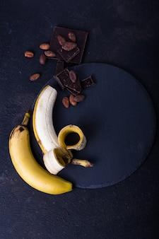 Żółty banan na czarnym tle. egzotyczna koncepcja żywności owoce minimalna koncepcja. leżał płasko.