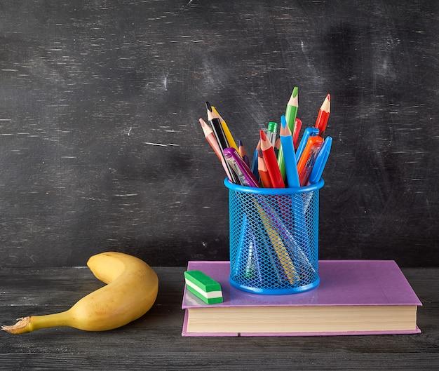 Żółty banan, niebieskie szkło biurowe z wielobarwnymi drewnianymi ołówkami
