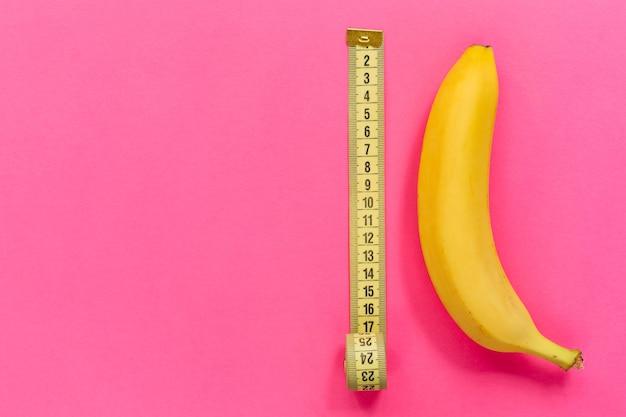Żółty banan z miarką na różowej powierzchni