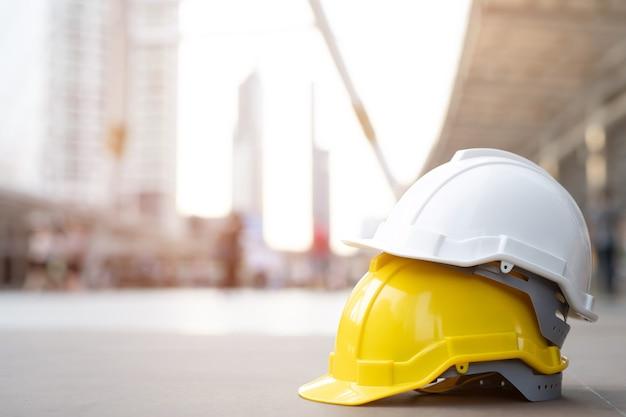Żółty, biały twardy kask ochronny w projekcie przy budowie budynku na betonowej podłodze w mieście. kask dla robotnika jako inżyniera lub pracownika