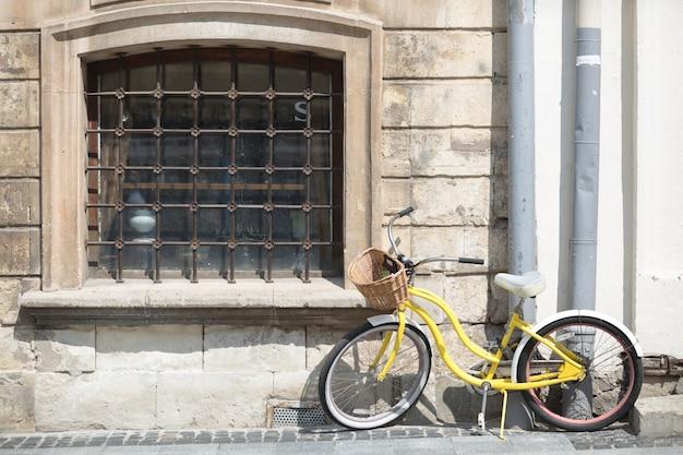 Żółty bicykl z koszem przed starą ścianą