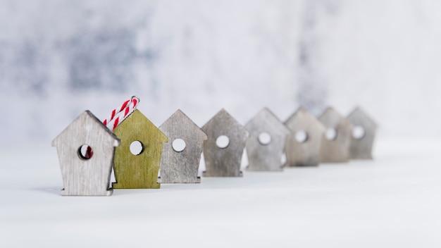 Żółty birdhouse stoi out od innych białych ptasich domów przeciw białemu tłu