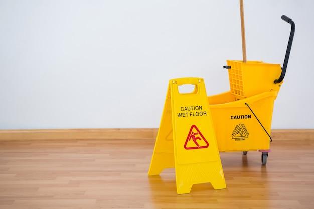 Żółty boad westchnienie z wiadrem mopa na podłodze przy ścianie