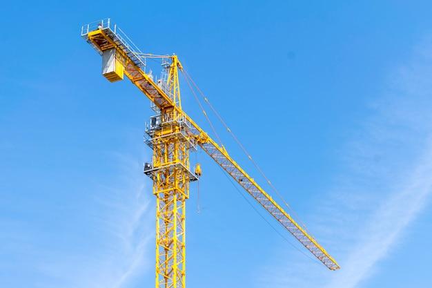 Żółty budowa żuraw na niebieskim niebie