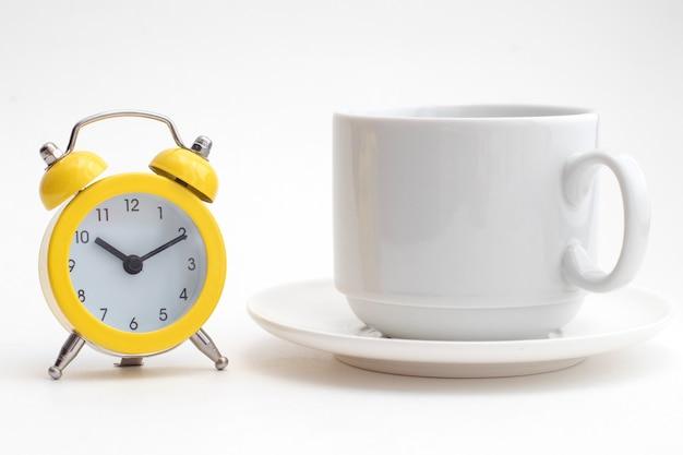 Żółty budzik i biała filiżanka kawy.