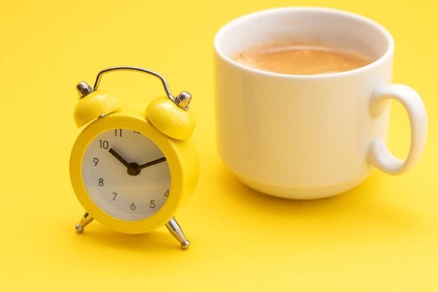 Żółty budzik z dzwonkiem i filiżanką świeżo parzonej kawy na żółtym tle.