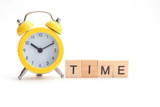 Żółty budzik z dzwonkiem i tekstem czasu z drewnianych kostek.