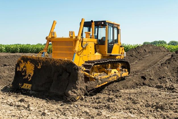 Żółty buldożer z gąsienicową ciągnikową pozycją w polu