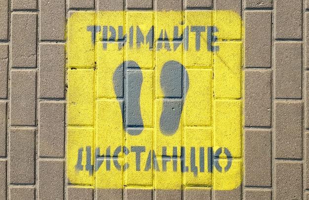 Żółty chodnik z ostrzeżeniem zachowaj dystans na chodniku