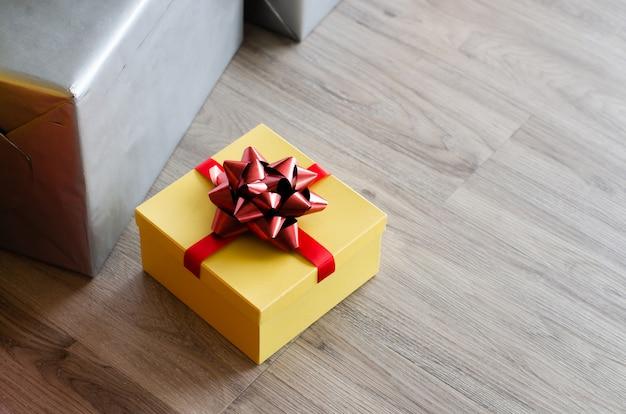 Żółty christmas gift box z czerwoną wstążką i copyspace na powitanie lub życzenia