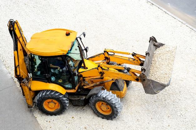 Żółty ciągnik prowadzi prace drogowe
