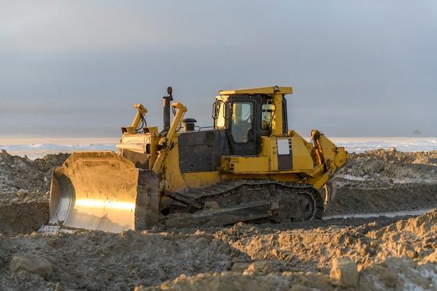 Żółty ciągnik w zimowej tundrze. budowa dróg. spychacz.