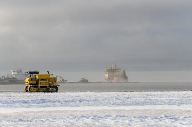 Żółty ciągnik w zimowej tundrze. budowa dróg.