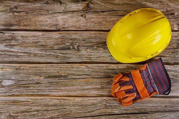 Żółty ciężkiego bezpieczeństwa odzieży hełma kapelusz w budowy pracy rzemiennych rękawiczkach w drewnianym tle